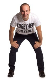 """A professional studio photo of a man in a white space wearing black pants and a T-shirt that says """"together it is possible"""""""
