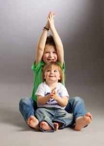 """A candid studio portrait of two young kids wearing jeans and """"save the future"""" T-shirts"""