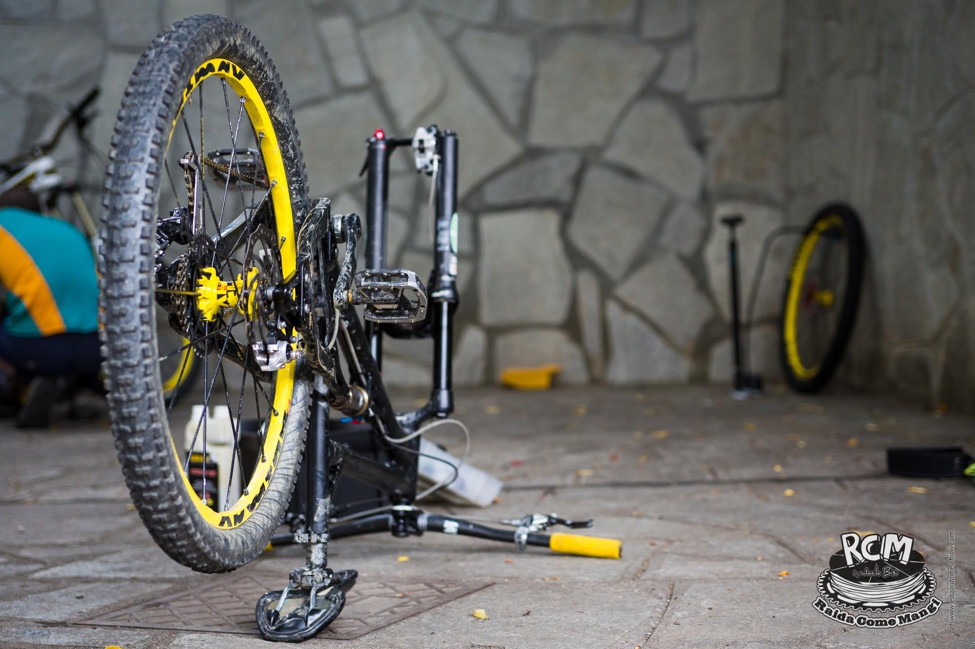 Una MTB capovolta a terra senza la ruota anteriore durante un pit stop meccanico