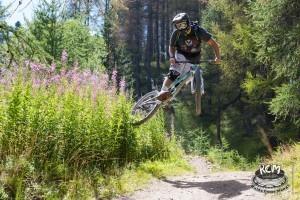 Un rider salta in sell alla sua MTB e fa un trick in volo toccando della vegetazione con la ruota posteriore