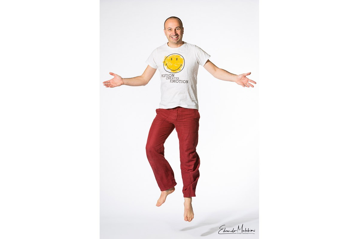 """A professional studio portrait of a barefoot man jumping in a white space wearing red pants and a T-shirt that says """"motion creates motion"""""""