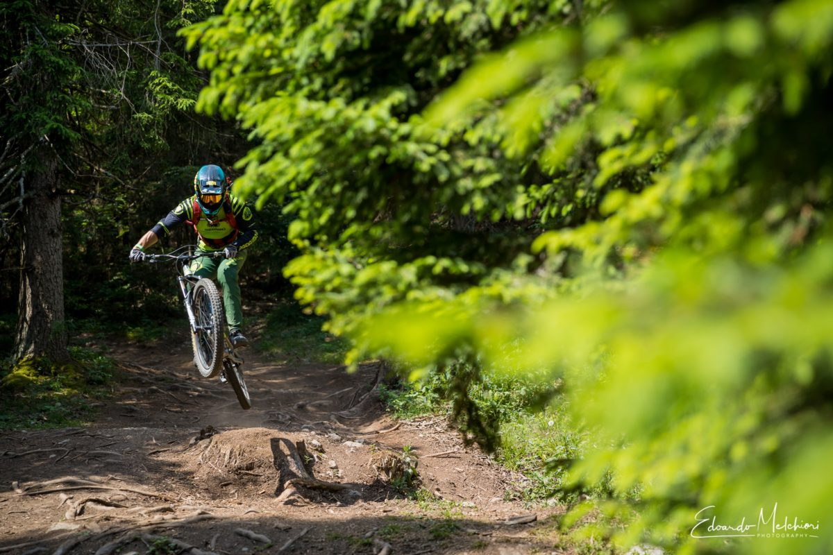 A MTB instructor jumps on the trails of Dolomiti Paganella Bike Park during a training camp