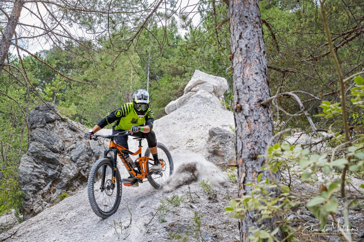 A MTB rider blows up some dirt in a steep line between rocks and trees