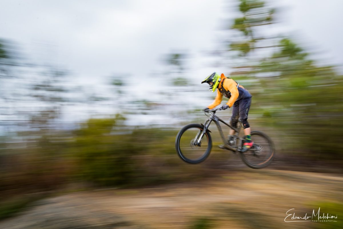 Pan image of a MTB rider jumping