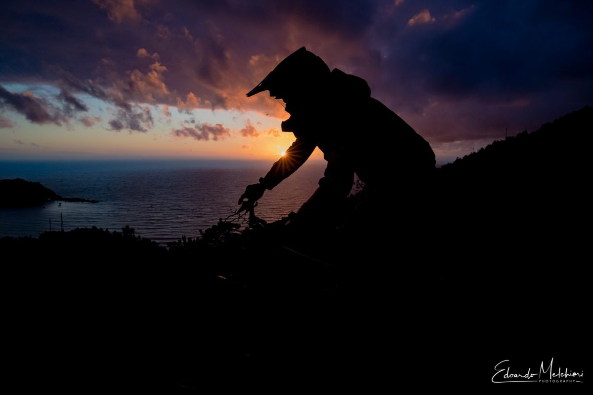 A MTBiker rides the last lap of the day as the sun sets on the sea.