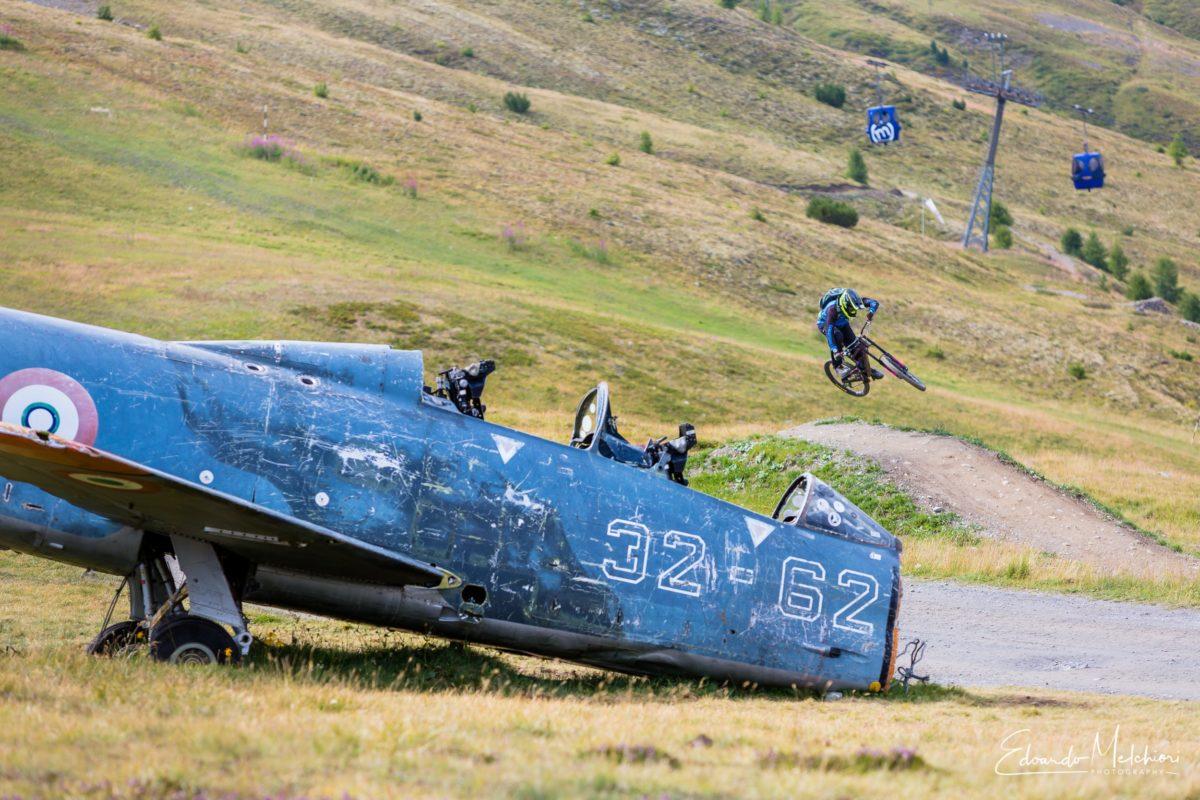 In primo piano il rottame di un aereo della seconda guerra mondiale mentre sullo sfondo Giacomo Bisi salta in mtb un panettone nel bike park del Mottolino a Livigno
