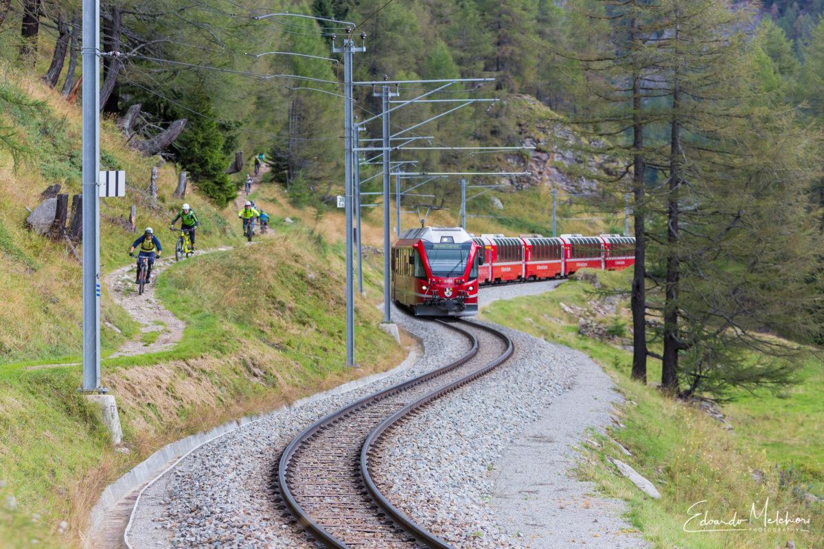 Il trenino del Bernina corre accanto al sentiero dove passano i rider in MTB