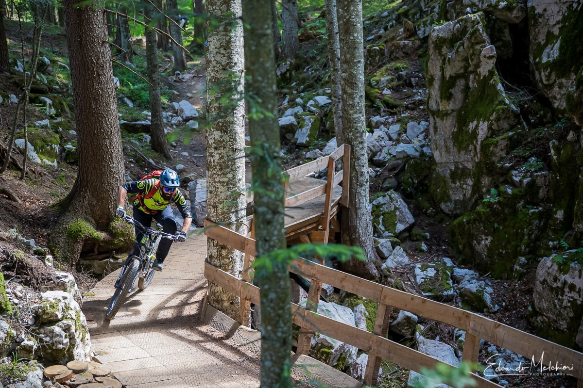 A MTB rider riding on a man made wooden structure in the Dolomiti Paganella Bike Park
