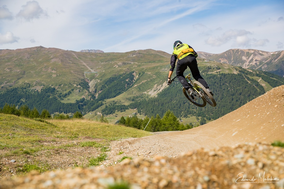 Fabio Crosetto istruttore RCM salta fuori da una sponda con le montagne sullo sfondo