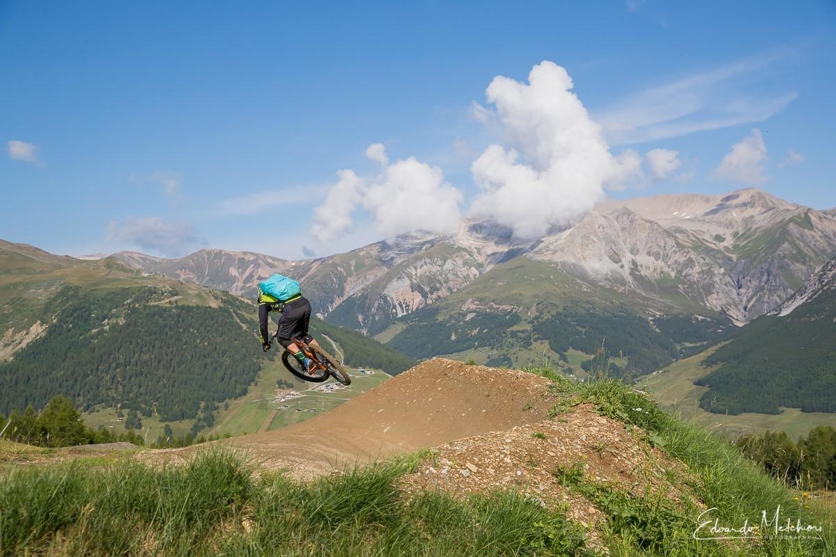 Jack Bisi istruttore RCM salta fuori da una sponda con le montagne sullo sfondo
