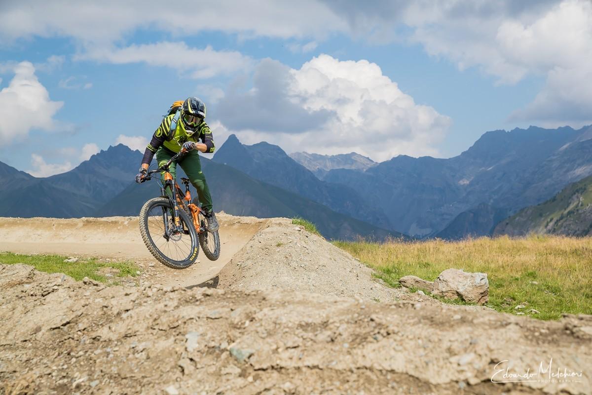 Giacomo Bisi istruttore MTB di RCM salta fuori da una sponda con montagne sullo sfondo