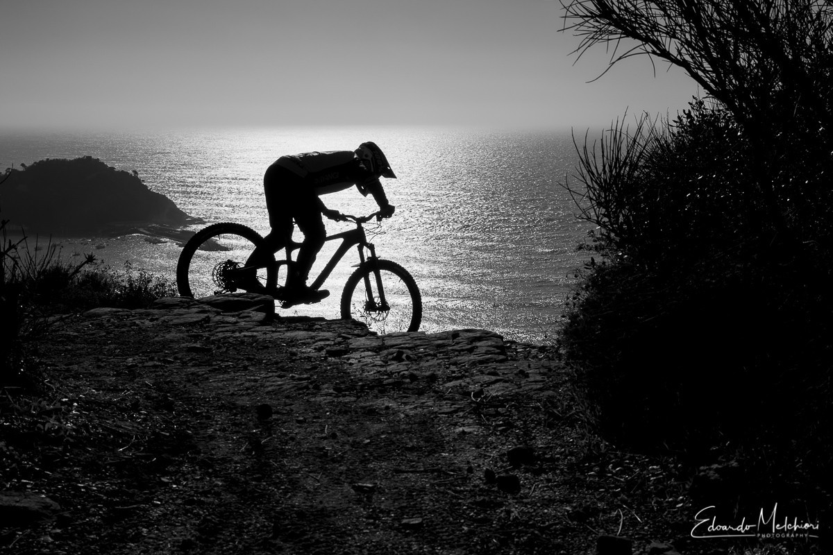 A black and white silhouette image of a MTB rider dropping on a rocky trail with the sea in the background.