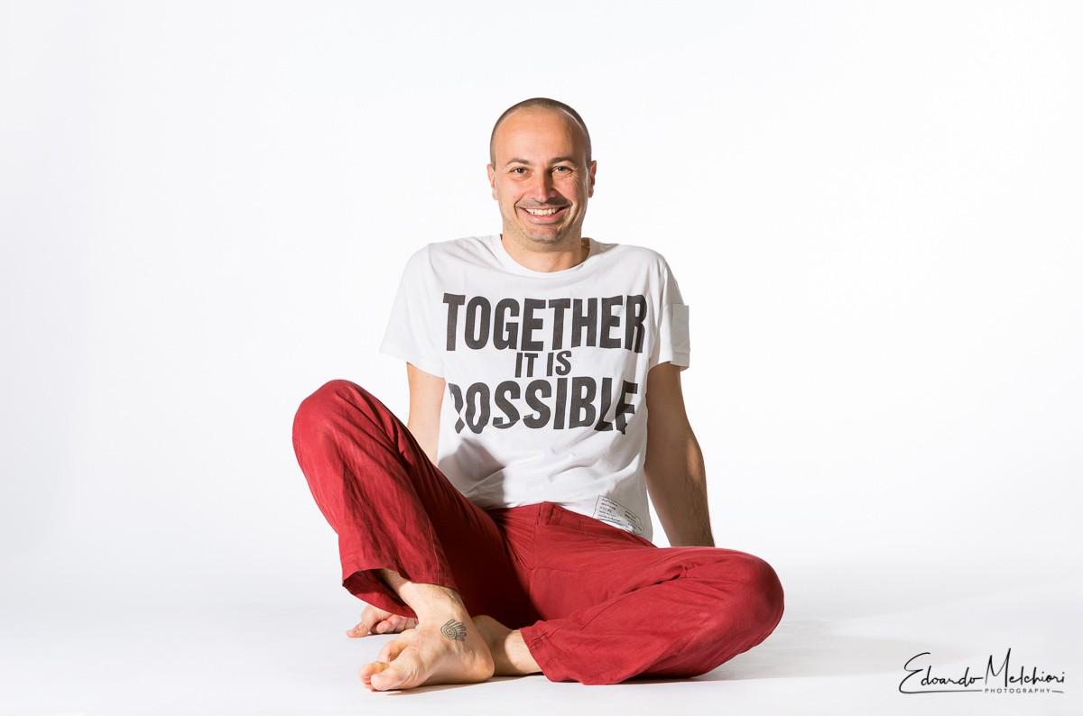 "A professional studio photo of a man sitting barefoot in a white space wearing red pants and a T-shirt that says ""together it is possible"""