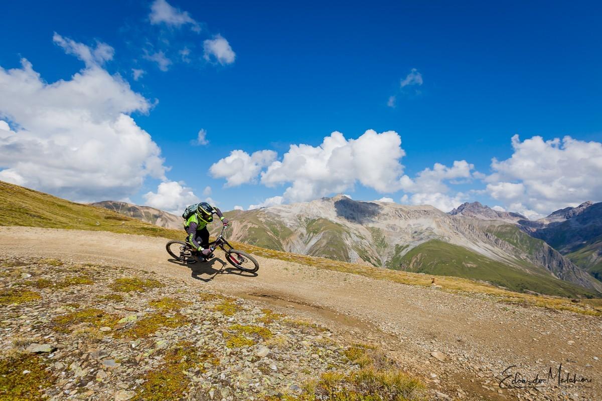 Giacomo Bisi istruttore MTB di RCM affronta una curva in MTB nel bike park con montagne sullo sfondo