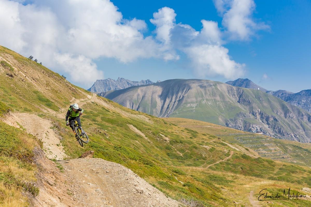 Giacomo Bisi istruttore MTB di RCM salta nel bike park con montagne sullo sfondo