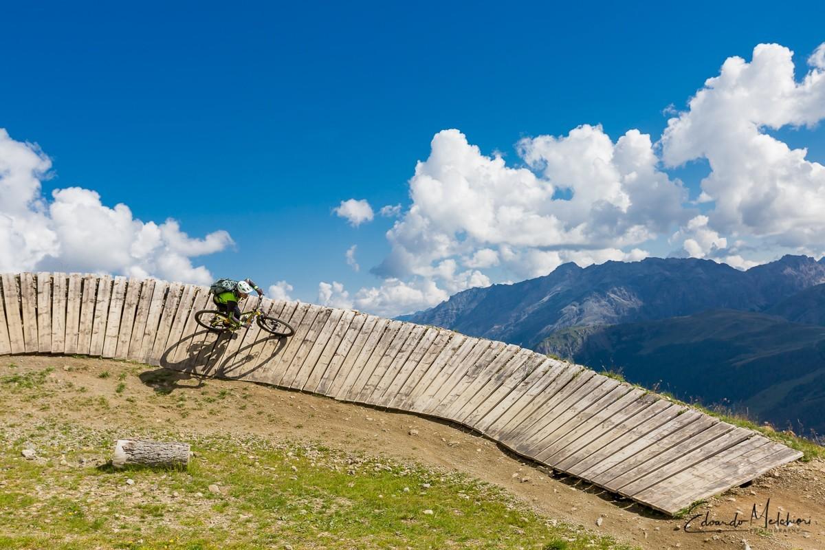 Giacomo Bisi istruttore MTB di RCM affronta una curva artificiale in legno nel bike park con montagne sullo sfondo