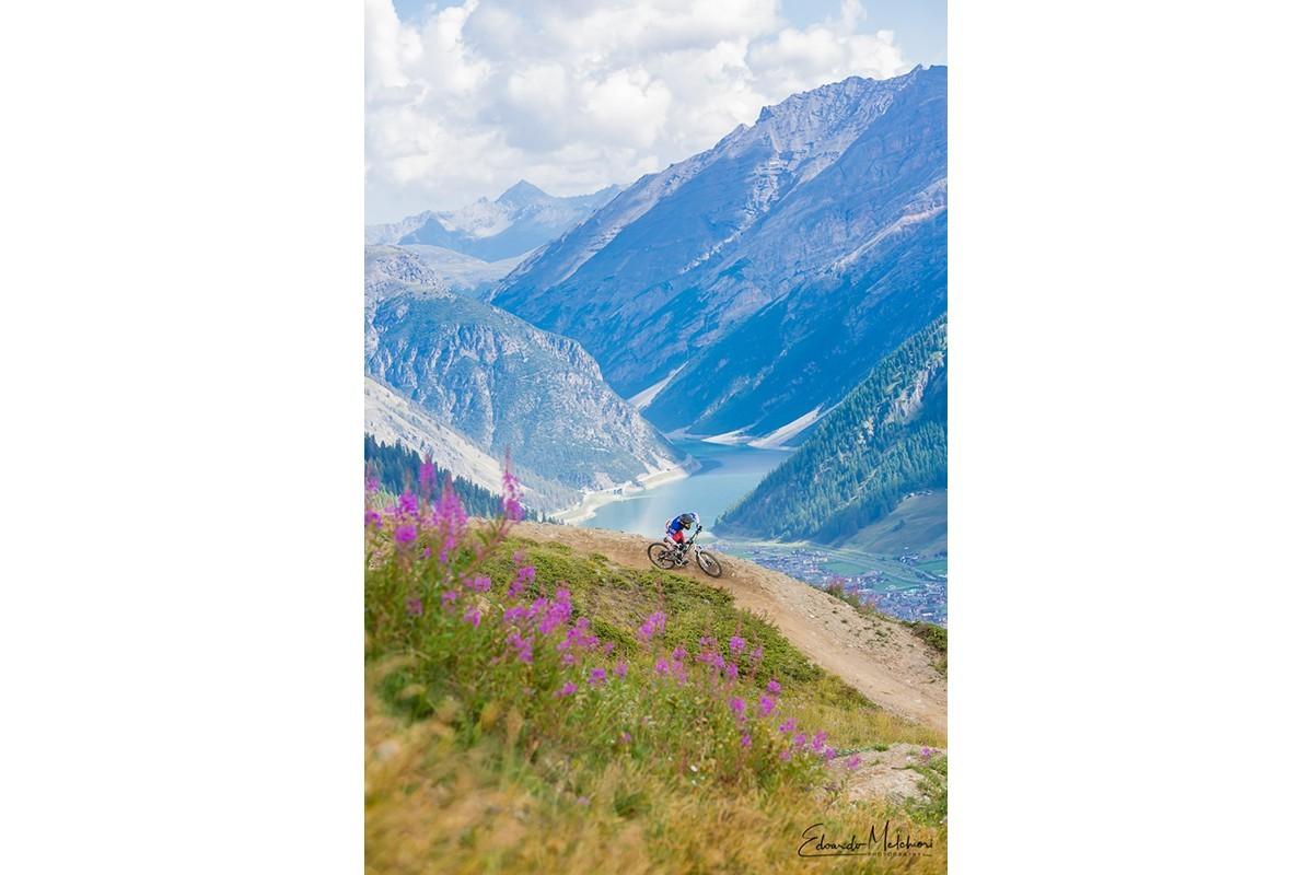 Un biker affronta una curva del bike park di Livigno con sullo sfondo in lago e le montagne