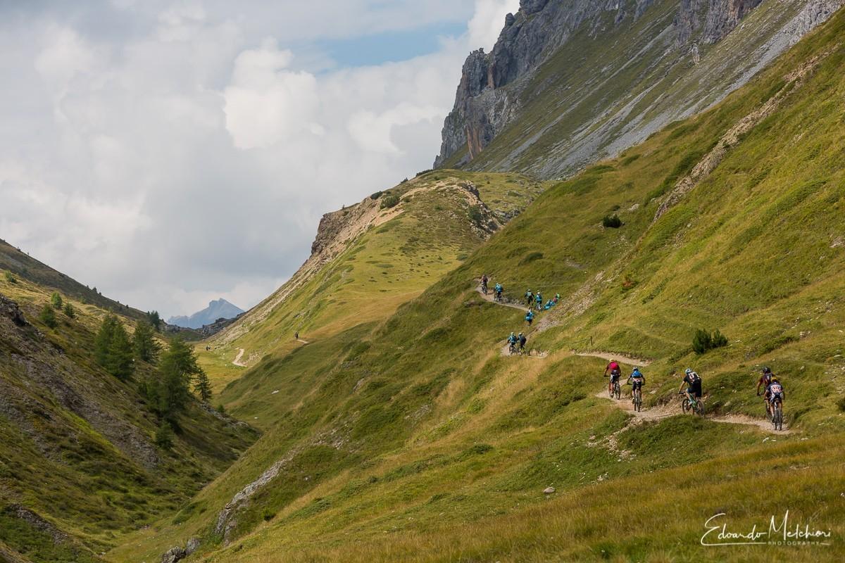Una fila di decine di biker si snoda lungo il sentiero sul fianco destro della valle