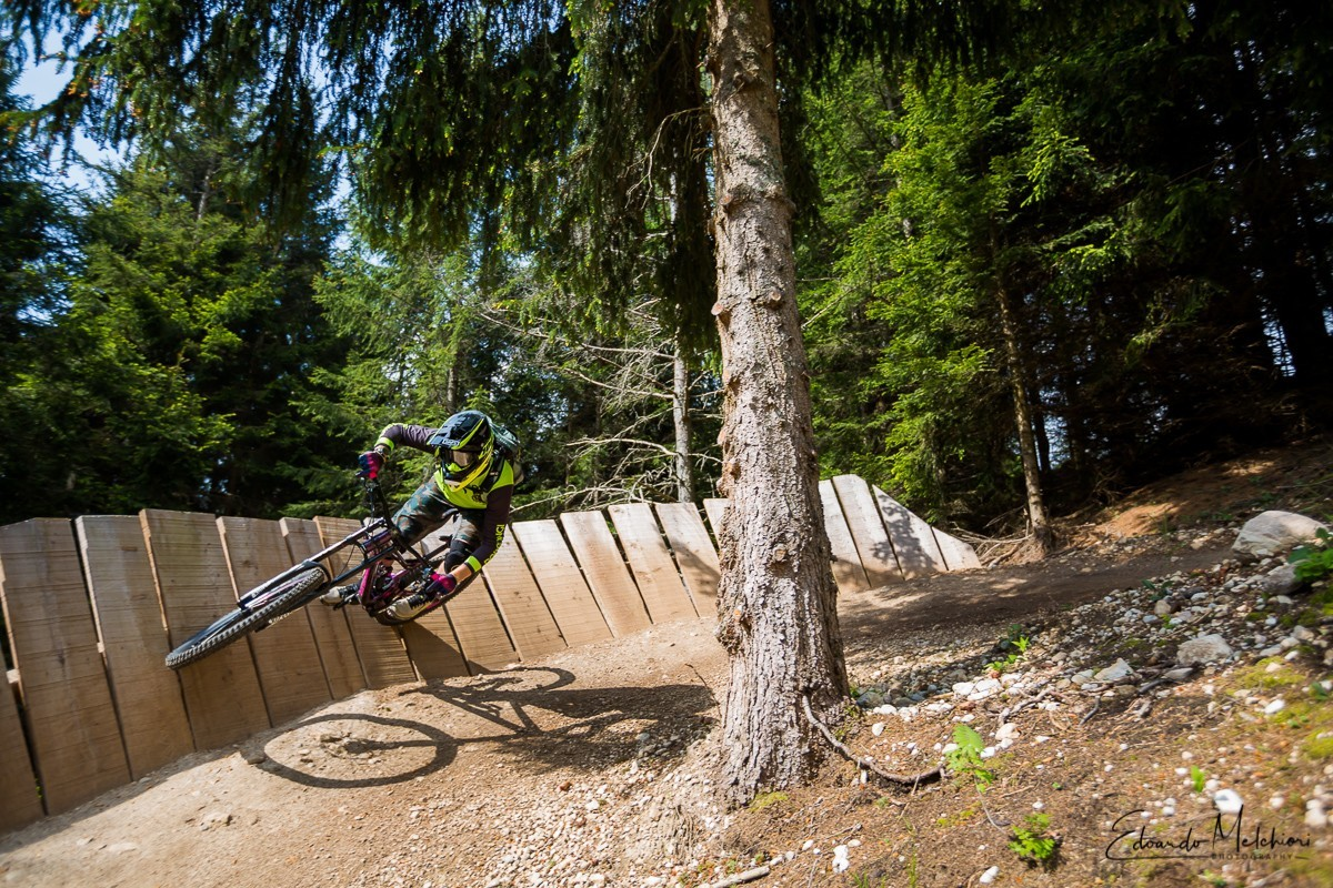 A MTB rider rides a wooden berm corner in the Bike Park of Dolomiti Paganella