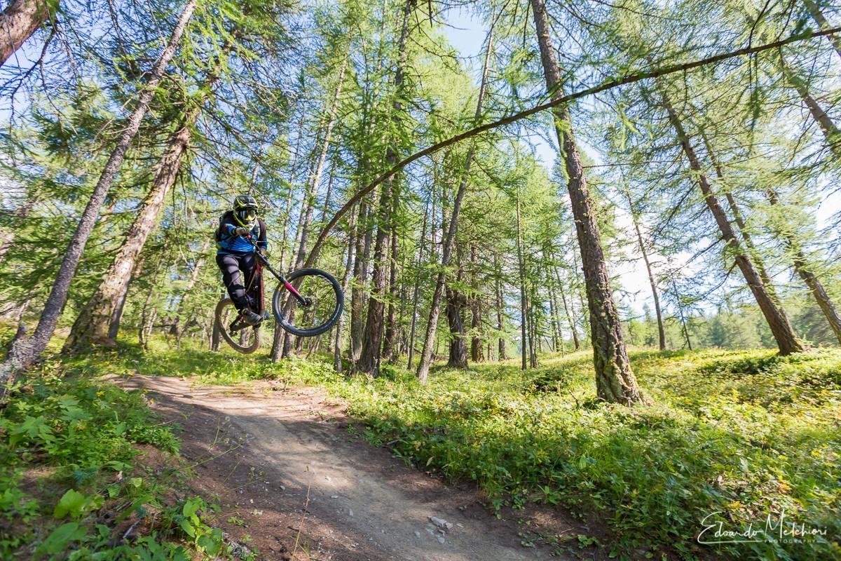 Un biker salta in MTB su un sentiero circondato dagli alberi a di Sauze d'Oulx