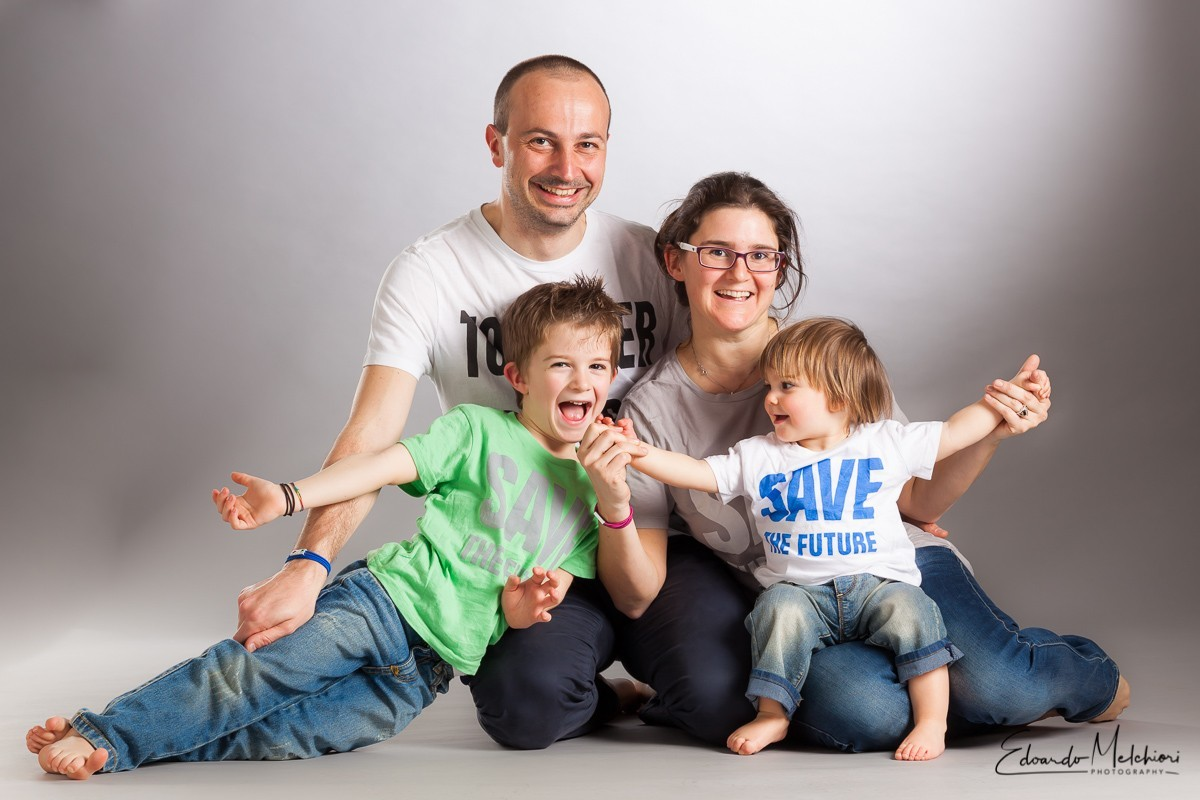 "A candid studio portrait of a family with father and mother and two young kids wearing jeans and ""save the future"" T-shirts"